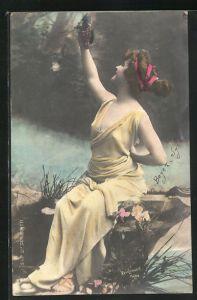 Foto-AK Atelier Reutlinger, Paris: Hübsche junge Dame im gelben Kleid mit Weintrauben