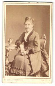 Fotografie J. C. Schaarwächter, Berlin, Portrait lächelnde Dame mit Hochsteckfrisur am Tisch sitzend