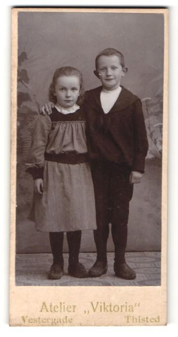 Fotografie Atelier Viktoria, Thisted, Portrait kleines Mädchen im hübschen Kleid u. Junge Arm in Arm
