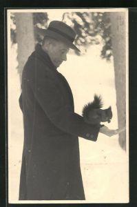AK Mann füttert ein Eichhörnchen