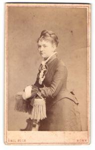 Fotografie Emil Koch, Bonn, Portrait wunderschönes Fräulein mit Flechtfrisur im gerüschten Kleid mit Schleifen