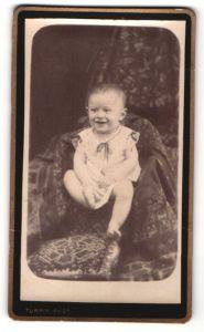 Fotografie L. Turpin, Orbec, Portrait niedliches Kleinkind im weissen Kleidchen auf Sessel sitzend