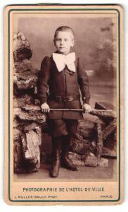 Fotografie L. Muller-Rault, Paris, Junge in Anzug mit Schleife u. Gürtel, Gerte in Hand