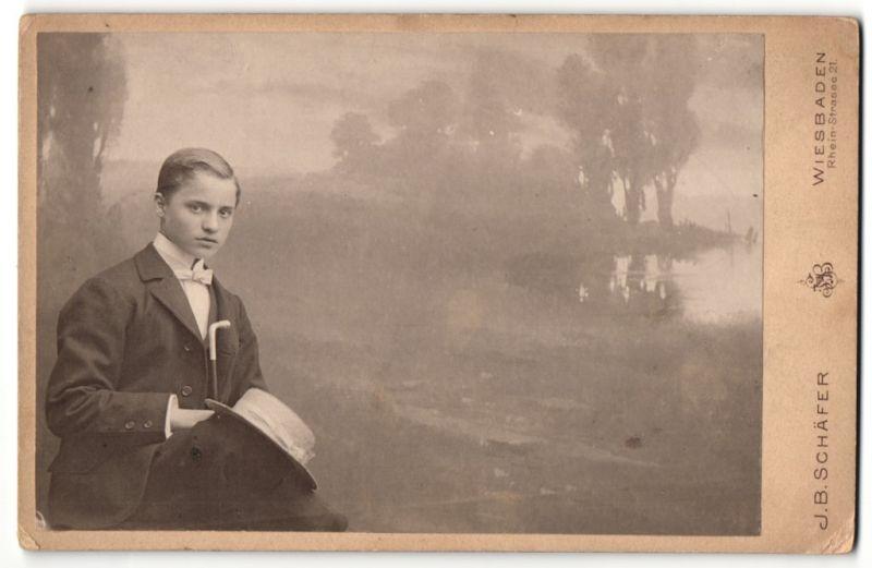 Fotografie J. B. Schäfer, Wiesbaden, Portrait Knabe in Anzug mit Fliege, Spazierstock und Hut