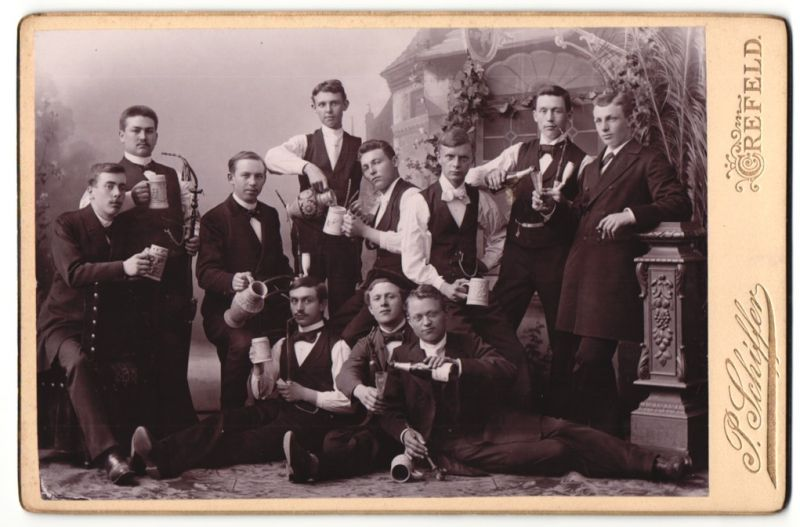 Fotografie P. Schiffer, Crefeld, Portrait junge Männer mit Sekt, Bier und Pfeife