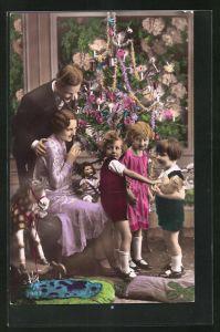 Foto-AK Familie mit Kindern u. Teddy, Puppe und Spielzeugpferd am Tannenbaum
