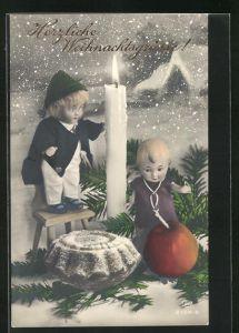 AK Zwei Puppen mit einem Apfel, einer Kerze und einem Kuchen im Schnee, Weihnachtsgruss