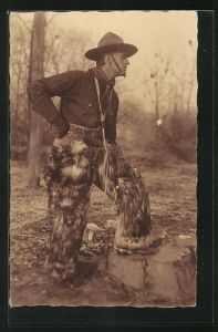 AK Variete, Mann in Pelzhose mit Revolver und Hut auf Baumstamm