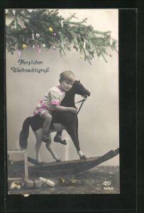 AK niedliches Kind auf einem Schaukelpferd, Herzlichen Weihnachtsgruss
