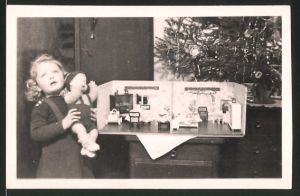 Fotografie Weihnachten, Mädchen mit Puppe und Puppenstube vorm Weihnachtsbaum