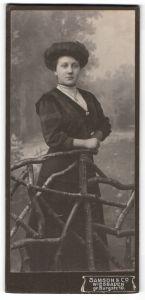 Fotografie Samson & Co, Wiesbaden, Portrait dunkelhaarige junge Schönheit im Kleid am Holzzaun stehend