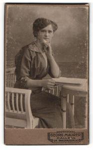 Fotografie Georg Maurer, Halle a / S., Portrait junge Dame im modischen Kleid mit Buch am Tisch sitzend