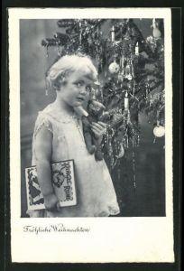 AK Mädchen neben Weihnachtsbaum hält Teddy im Arm, Weihnachtskarte