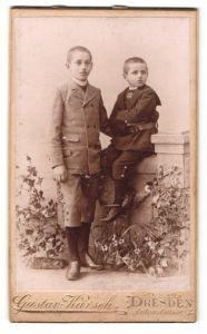 Fotografie Gustav Karsch, Dresden, Portrait zwei kleine Jungen in hübscher Kleidung an einer Mauer