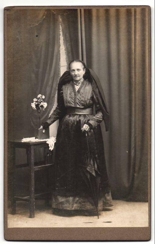 Fotografie betagte Dame in schwarz mit traditioneller Haarlschleife und Schirm