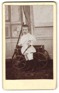 Fotografie unbekannter Fotograf und Ort, Portrait Bub mit Bollerwagen