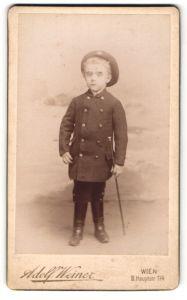 Fotografie Adolf Weiner, Wien, Portrait frecher blonder Bube mit Stab und Mütze im Anzug