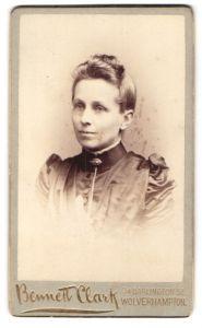 Fotografie Bennett Clark, Wolverhampton, Portrait lächelnde Dame mit Hochsteckfrisur u. Kragenbrosche