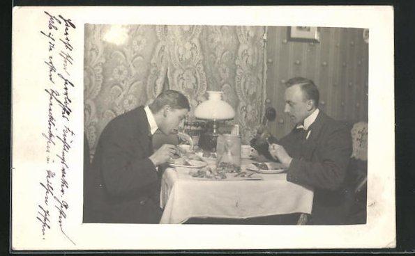 Foto-AK Zwei Herren bei einer reichhaltigen Mahlzeit