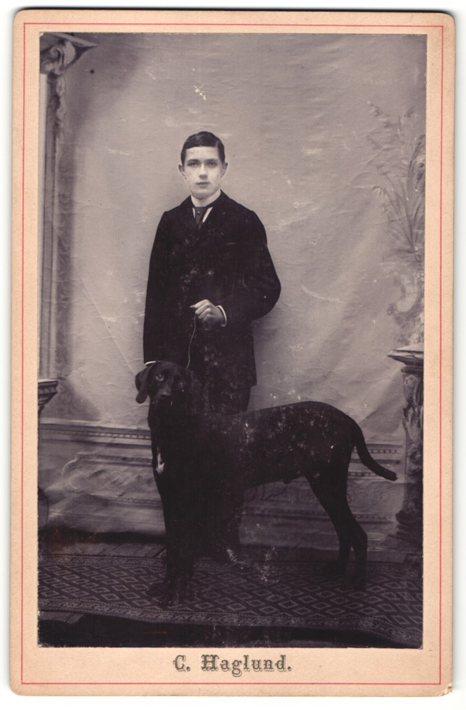 Fotografie C. Haglund, Ort unbekannt, Bursche mit Hund Labrador im Foto-Atelier
