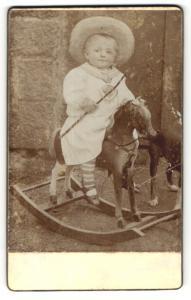 Fotografie Fotograf und Ort unbekannt, Baby mit Hut auf Schaukelpferd sitzend