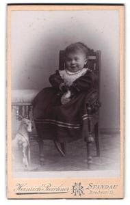 Fotografie Heinrich Reichner, Berlin-Spandau, Portrait lachendes kleines Mädchen mit Spielzeugpferd
