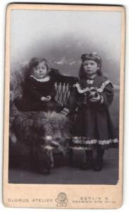 Fotografie Atelier Globus, Berlin-S., Portrait Kleinkind im hübschen Kleid auf Stuhl sitzend u. Schwester mit Ball