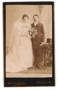Fotografie Adolf Schiller, Frankfurt a / M., Portrait bürgerliches Paar in hübscher Hochzeitskleidung mit Blumenstrauss