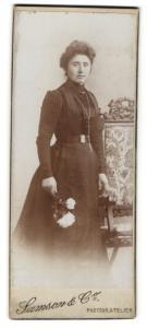 Fotografie Samson & Co., unbekannter Ort, Portrait bürgerliche Dame im eleganten Kleid mit Blumen an Stuhl gelehnt