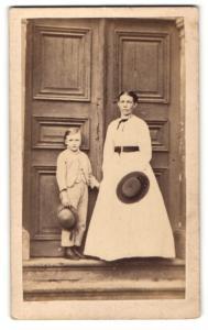 Fotografie G. Hisgen, Lich, Dame mit Gürtel um Taille und Hut haltend mit Jungen Hut haltend vor Tür