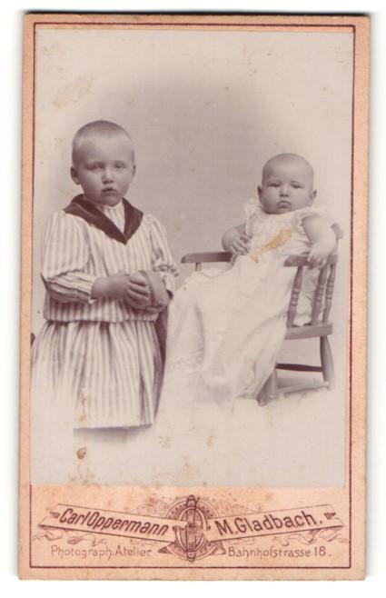 Fotografie Carl Oppermann, M. Gladbach, Portrait niedliches Baby im weissen Kleid im Hochstuhl sitzend u. Schwester