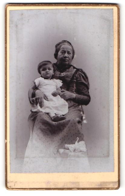 Fotografie unbekannter Fotograf und Ort, Portrait ältere Dame im zeitgenöss. Kleid mit Kind im Arm