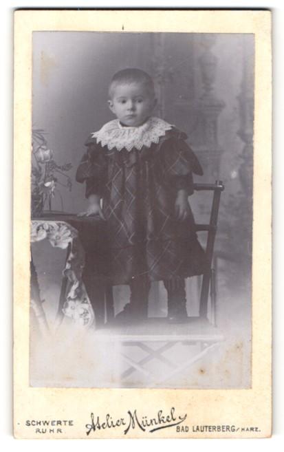 Fotografie Atelier Münkel, Bad Lauterberg / Mainz, Portrait niedliches Kleinkind im hübschen Kleid auf Stuhl stehend