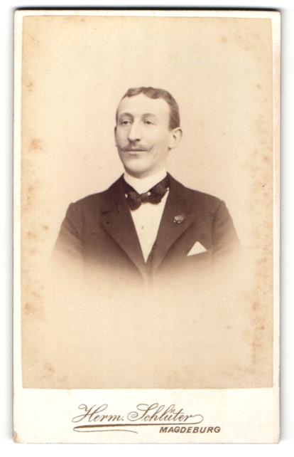 Fotografie Herm. Schlüter, Magdeburg, Portrait charmanter Herr mit Fliege im Anzug