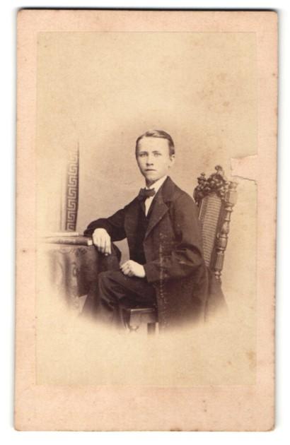 Fotografie G. Steffens, Berlin, Portrait charmanter junger Herr im Anzug mit Buch am Tisch sitzend