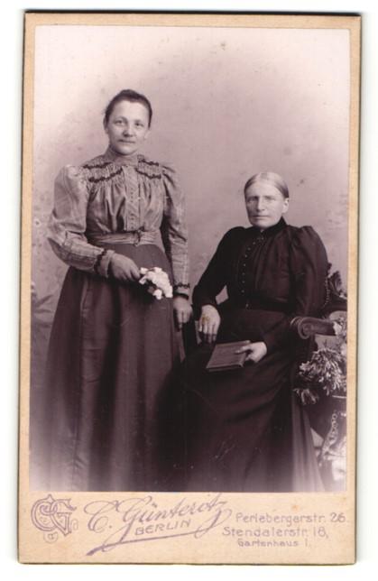 Fotografie Carl Günteritz, Berlin, Portrait ältere Dame mit Buch auf Stuhl sitzend u. junge Dame mit Blumen