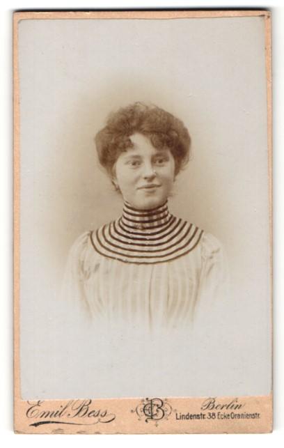 Fotografie Emil Bess, Berlin, Portrait junge lächelnde Dame in modischer Kleidung mit Kragenbrosche