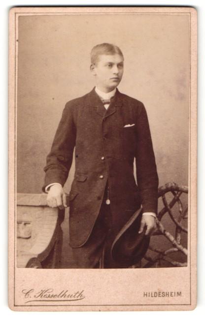 Fotografie C. Kesselhuth, Hildesheim, Portrait junger Herr mit Fliege u. Hut in zeitgenöss. Kleidung an Sockel gelehnt