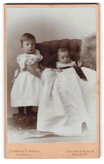 Fotografie Francois Cornand, Berlin-W., Portrait niedliches Baby im weissen Kleid auf Sessel sitzend u. Schwester
