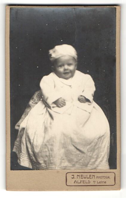 Fotografie J. Neulen, Alfeld a / Leine, Portrait niedliches Kleinkind in hübscher Kleidung auf Tisch sitzend