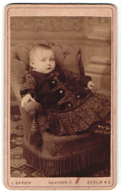 Fotografie J. Baruch, Berlin N. O., Portrait niedliches Kleinkind im hübschen Kleid im Sessel sitzend