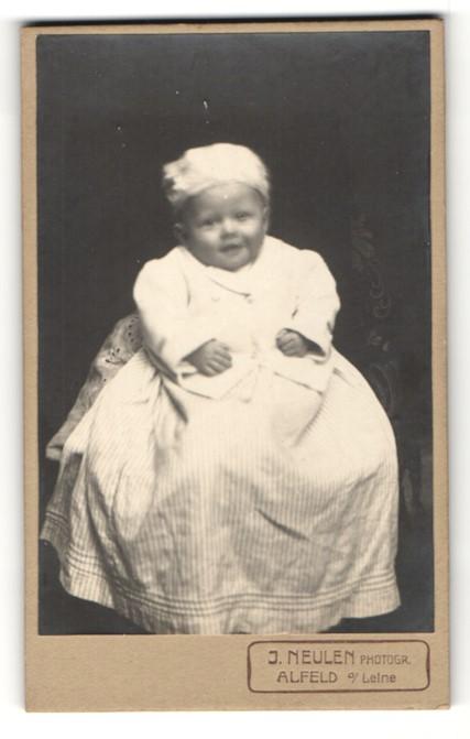 Fotografie J. Neulen, Alfeld a / Leine, Portrait niedliches Kleinkind im hübschen Kleid auf Tisch sitzend