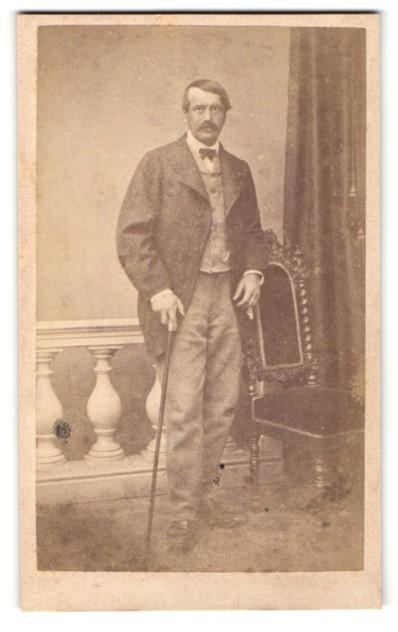 Fotografie A. Bammert, München, Portrait charmanter Herr in zeitgenössischer Kleidung mit Stock an Stuhl gelehnt