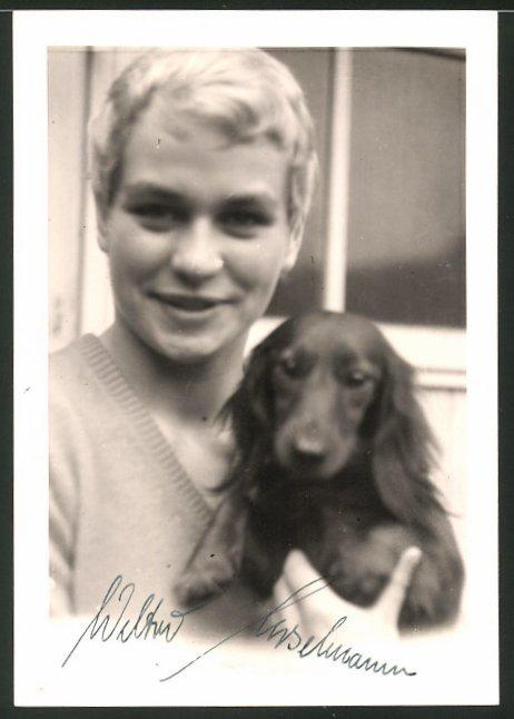 Fotografie blonder Bursche mit Hund - Dackel im Arm 0