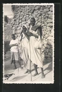 AK Afrikanische Hirten stehen vor einer Steinmauer, afrikanische Volkstypen