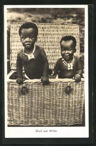 AK Afrikanische Kleinkinder blicken aus einem grossen Korb, afrikanische Volkstypen