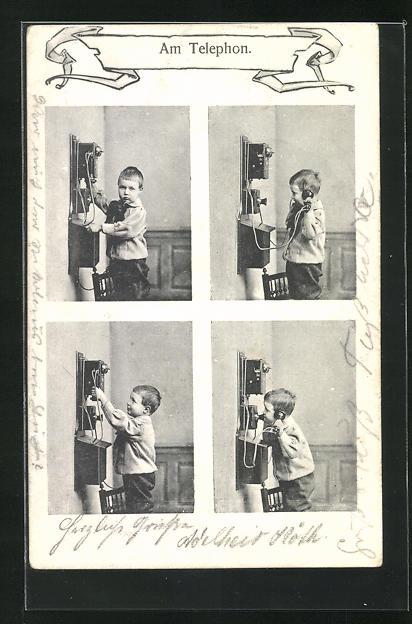 AK Kleiner Junge steht am Telefon und versucht zu telefonieren