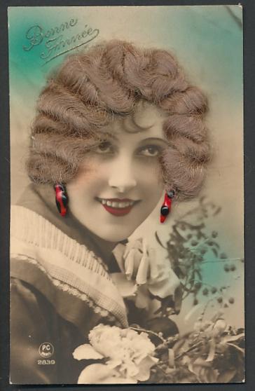 Echt-Haar-AK Schönheit mit blondgelocktem Haar und schwarz-roten Ohrringen