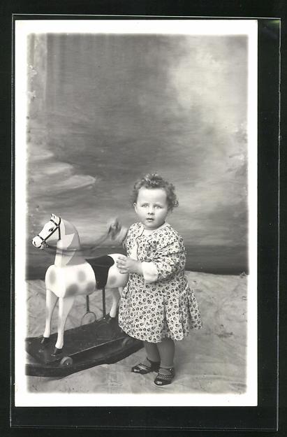 AK kleines Mädchen neben einem Schaukelpferd