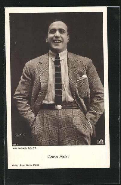AK Schauspieler Carlo Aldini lächelnd mit Händen in den Taschen